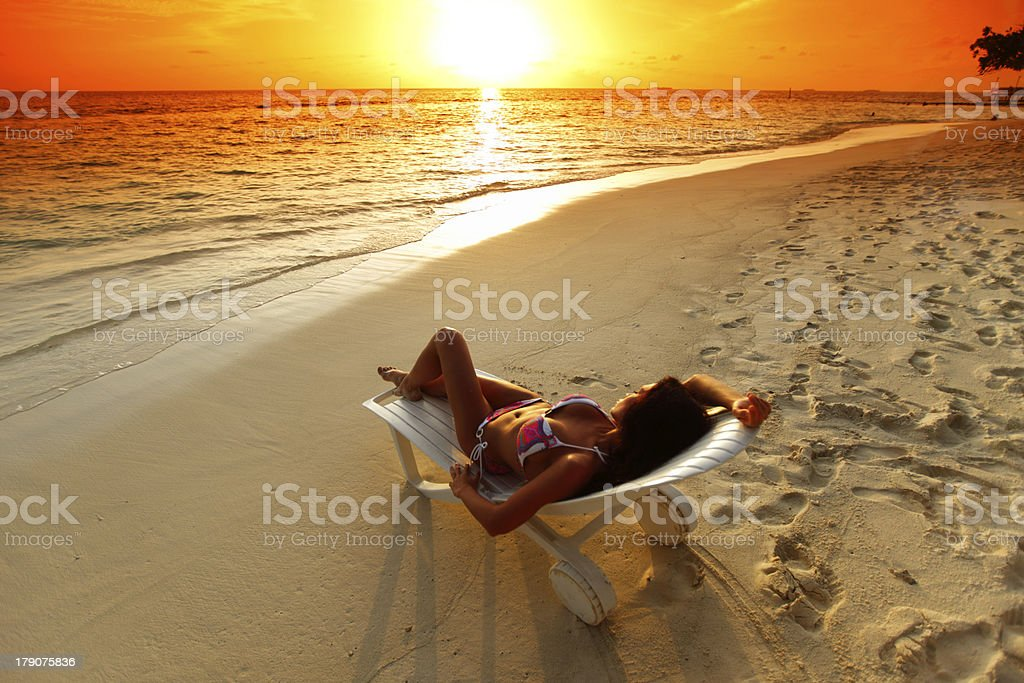 Woman in chaise-lounge relaxing on beach royalty-free stock photo