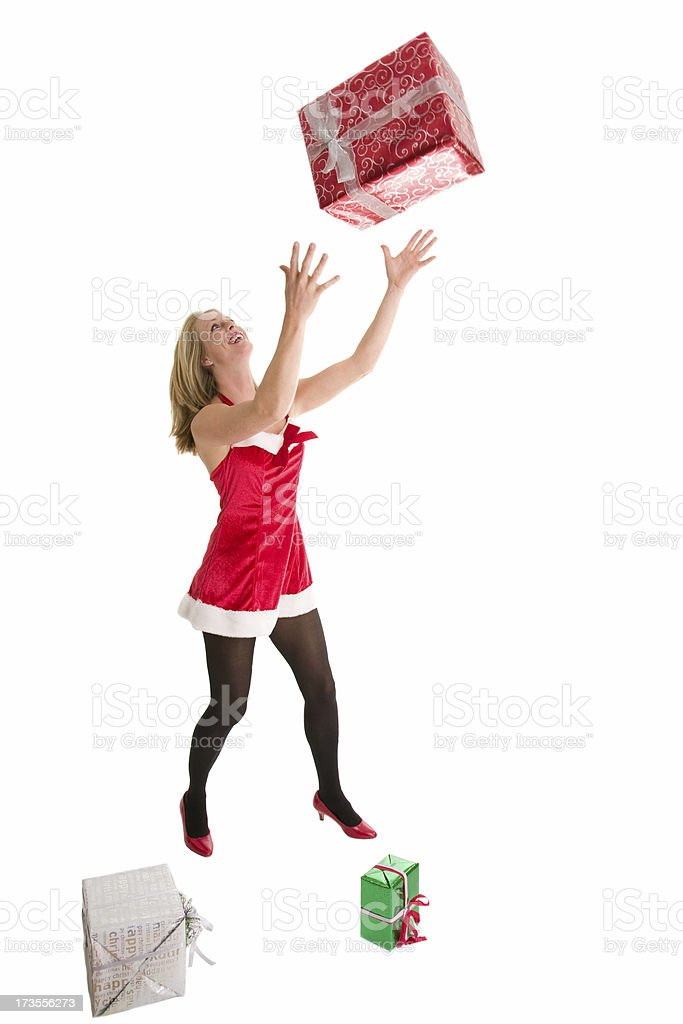 Woman in Christmas outfit catching presents royalty-free stock photo