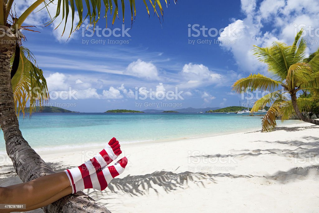 woman in Christmas socks relaxing at a Caribbean beach royalty-free stock photo