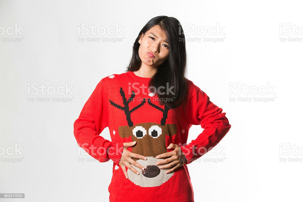 Woman in Christmas sweater she has eaten too much food stock photo