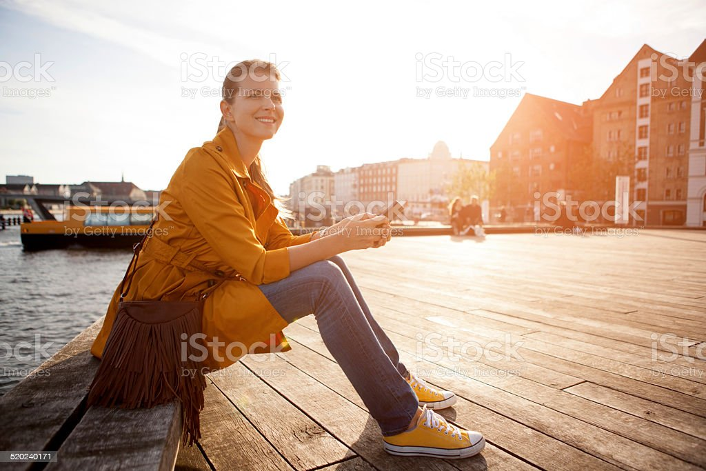 Woman in city enjoyng sun. stock photo
