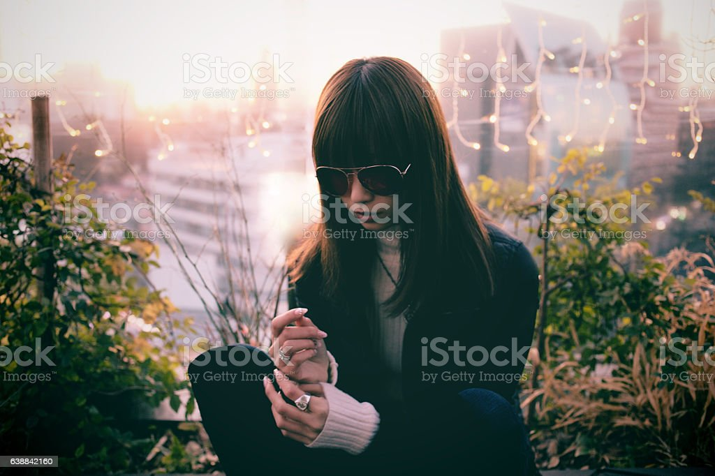 Woman in city garden at sunset stock photo