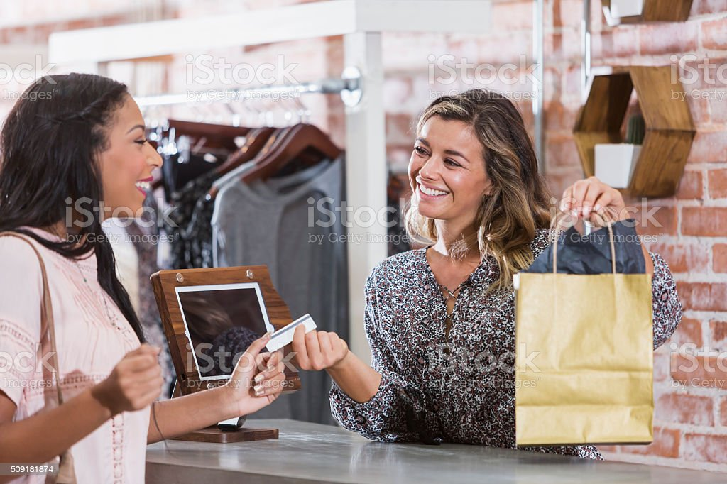 Woman in clothing store paying at checkout counter stock photo
