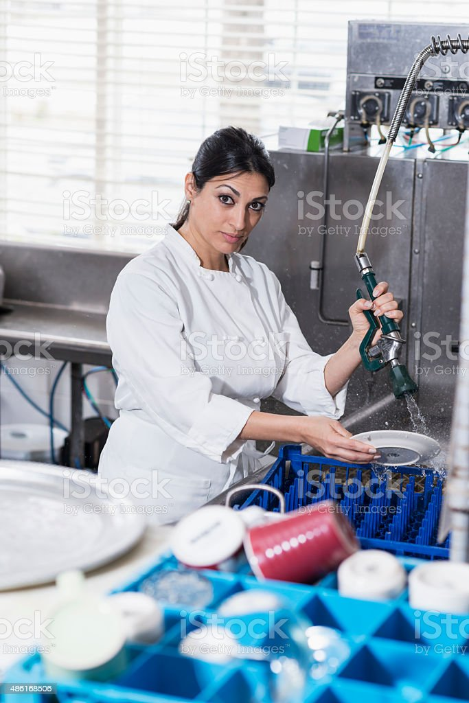 Woman in commercial kitchen at sink cleaning dishes stock photo