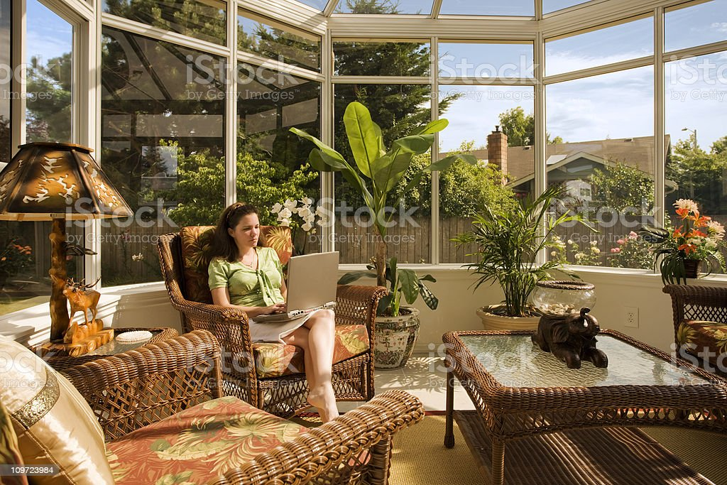 Woman in Conservatory Working on Laptop stock photo