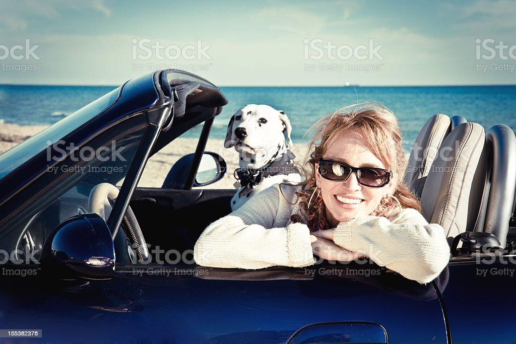 Woman in convertible with pet stock photo