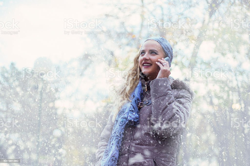 Woman in covered park using smartphone and smiling stock photo