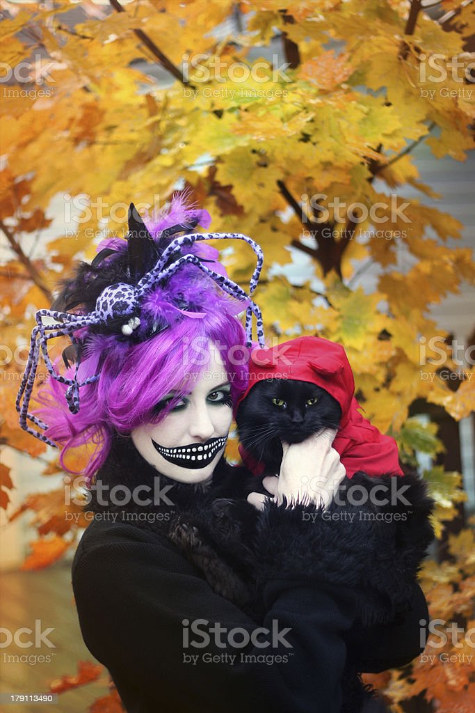 Woman in Creepy Halloween Costume and Black Cat stock photo