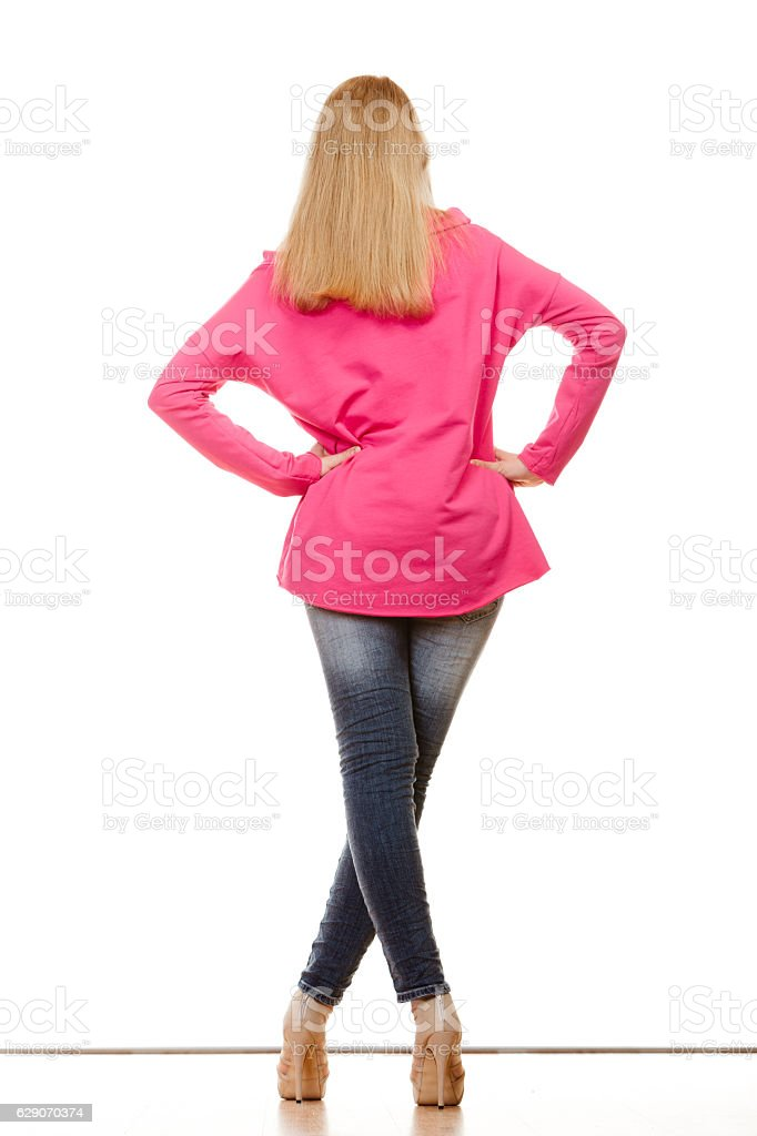 woman in denim pants high pink shirt back view stock photo