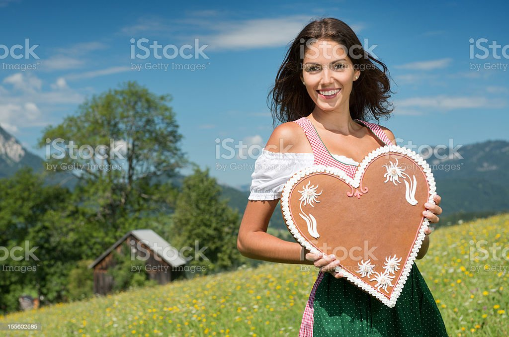Woman in Dirndl Fashion holding a Lebkuchen Gingerbread Heart (XXXL) stock photo