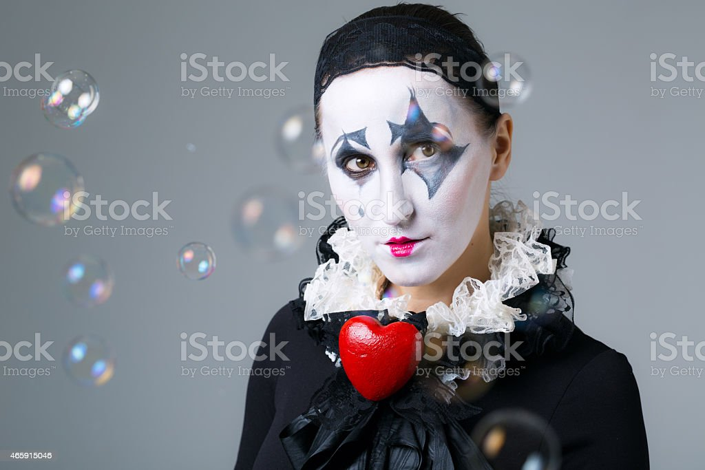 Woman in disguise harlequin with soap bubbles in the background stock photo