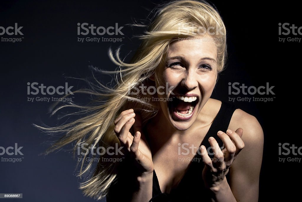 Woman in dramatic lighting screaming stock photo