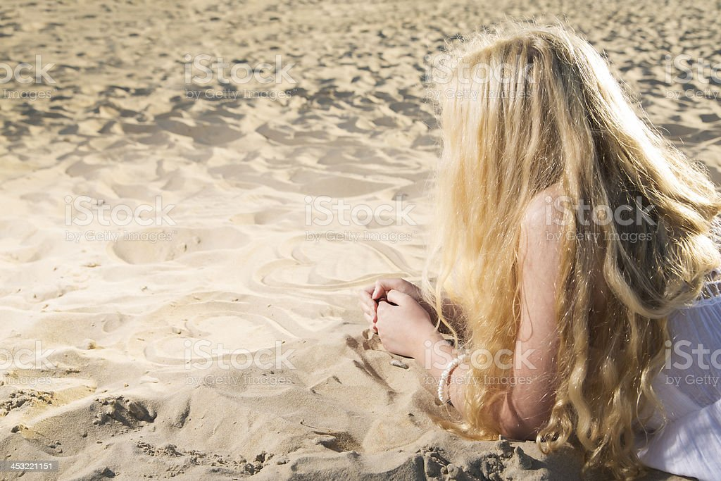Woman in dress draw hearts on sand royalty-free stock photo