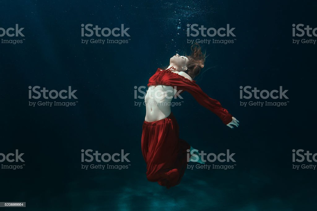 Woman in dress on the bottom underwater. stock photo
