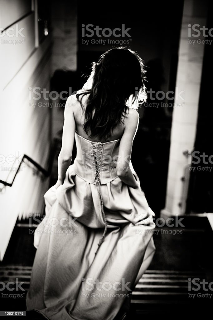 Woman in dress walking downstairs, rear view, black and white stock photo