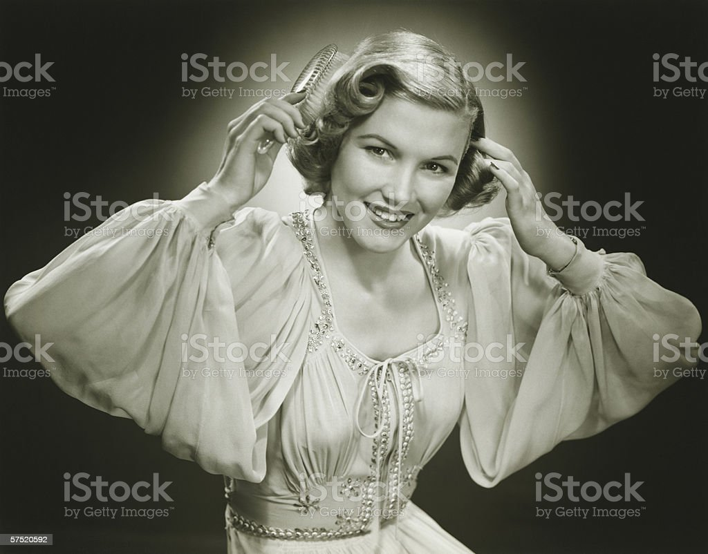 Woman in evening dress brushing hair, (B&W), portrait stock photo
