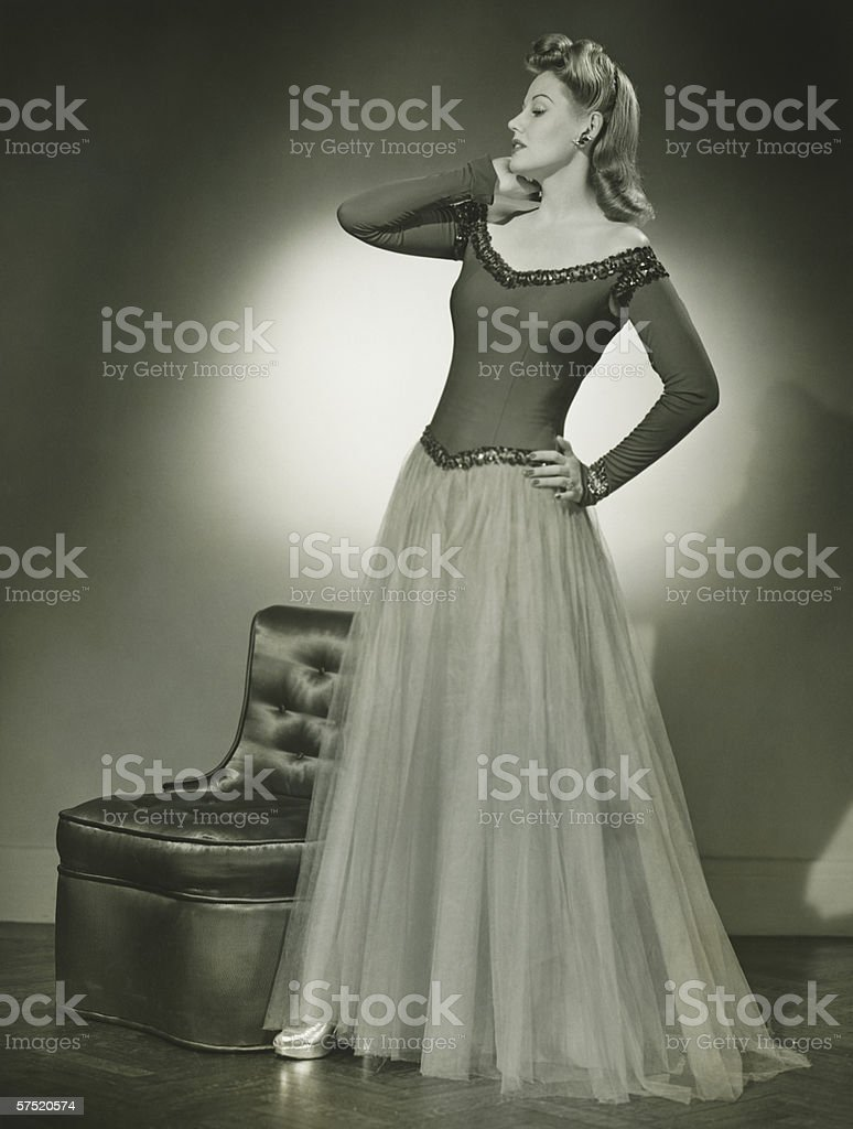 Woman in evening dress standing indoors, holding hand on cheek, (B&W) stock photo