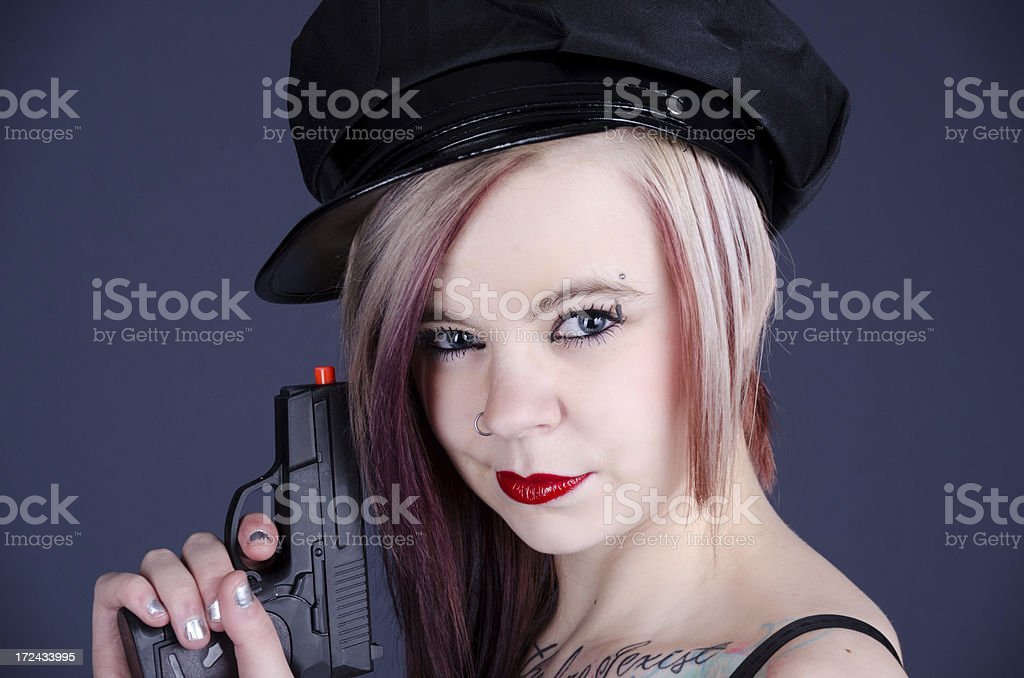 Woman in fake cop hat with toy gun. stock photo