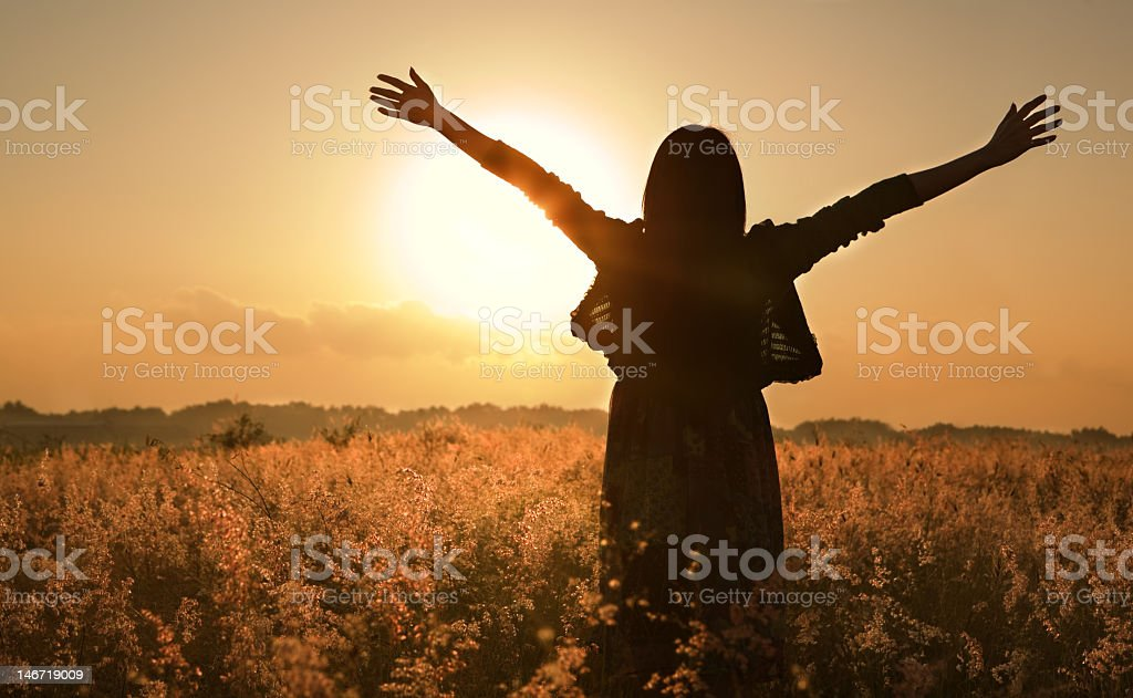 Woman in field with low sun behind stock photo