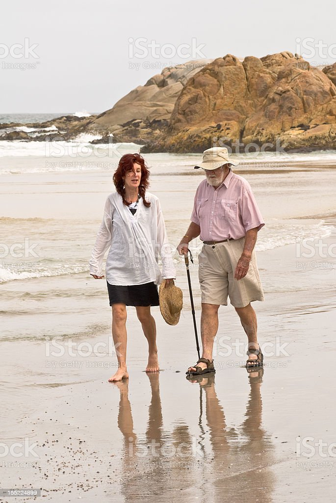 Woman in fifties talking with senior male on beach stock photo