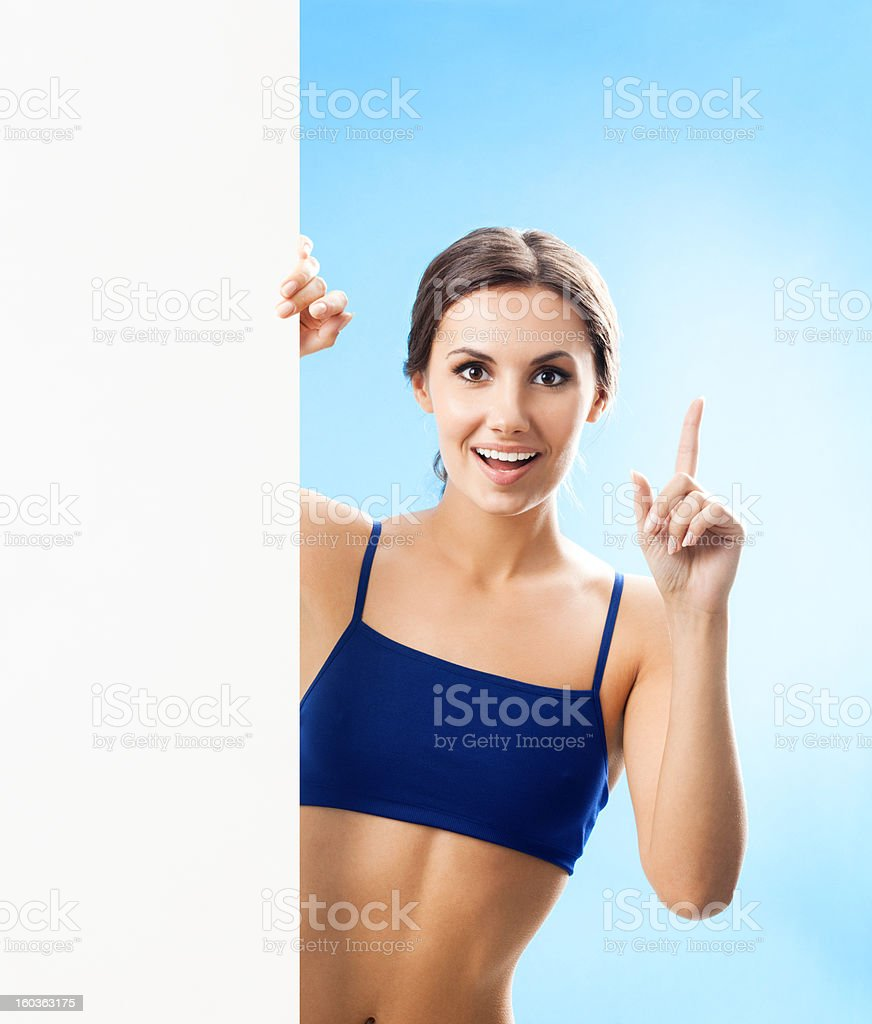 Woman in fitnesswear showing signboard, over blue royalty-free stock photo