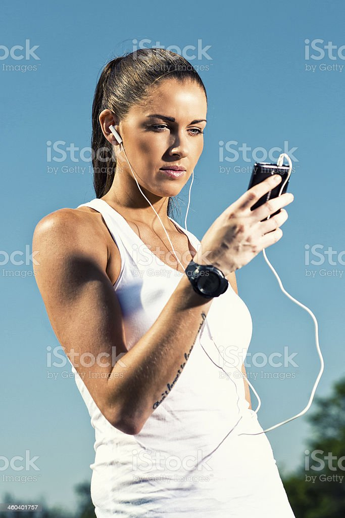 Woman in fittness clothes holds a mobile phone royalty-free stock photo