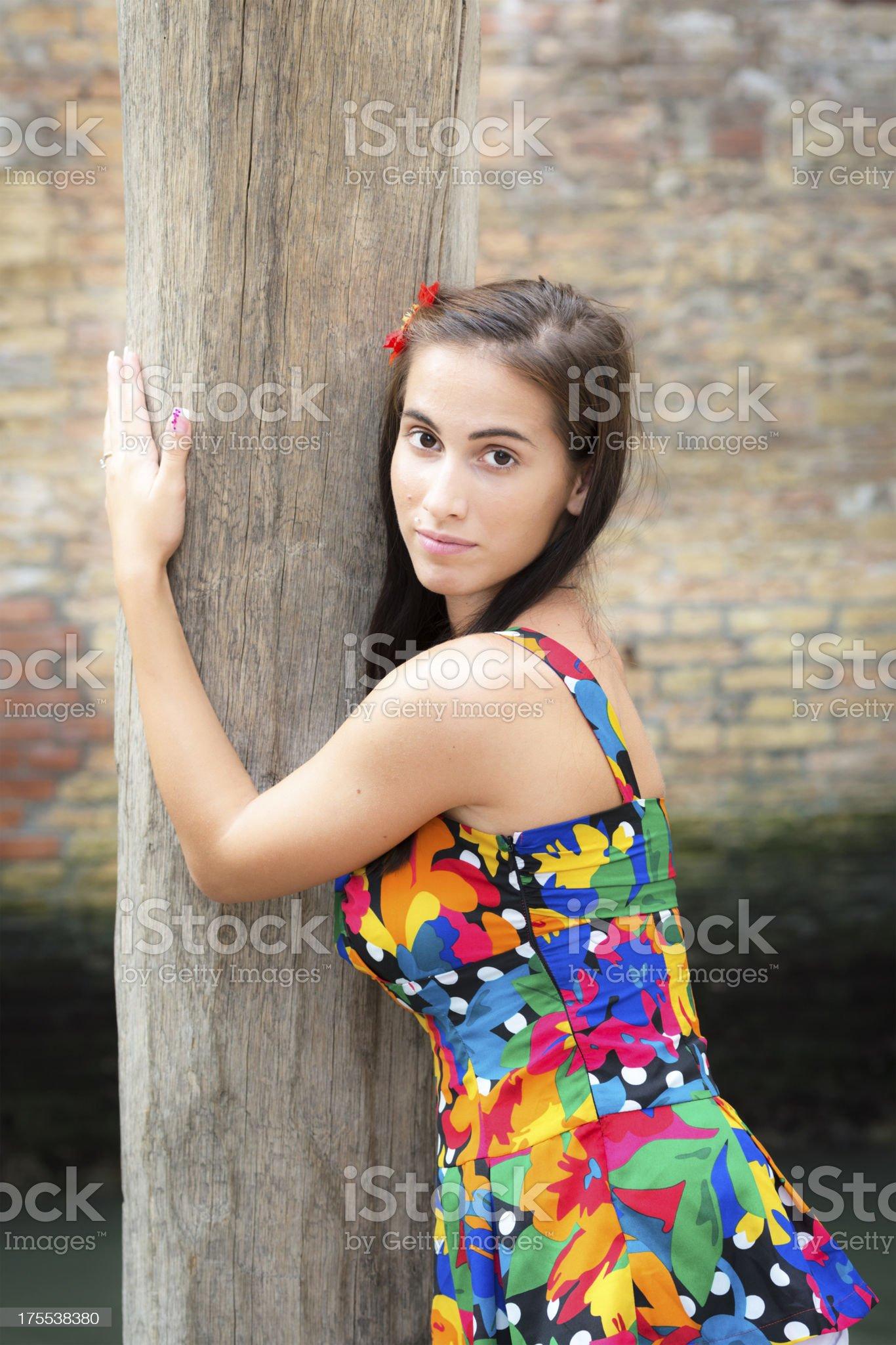 Woman in Floral Pattern Dress Embracing Wood Pillar, Venice Italy royalty-free stock photo