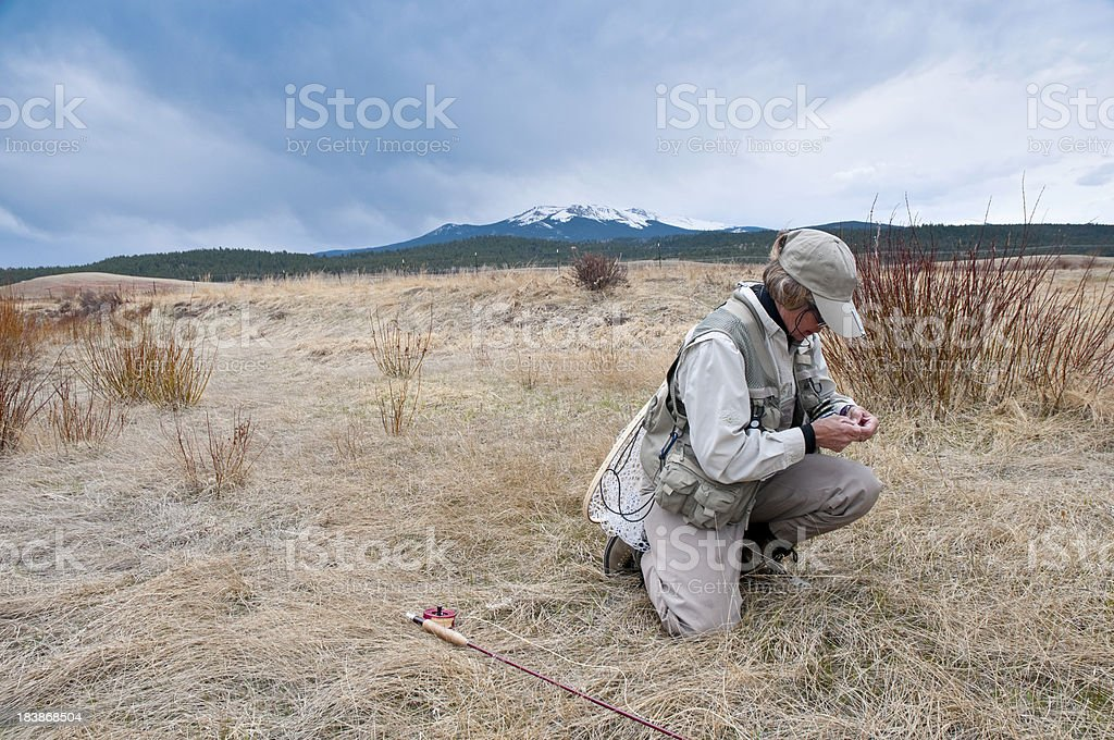 Woman in Fly-Fishing Gear on a Stormy Day stock photo