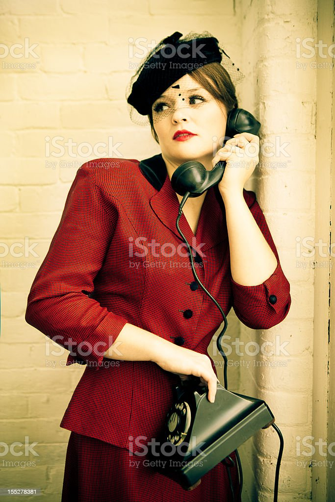 Woman in forties clothing holding a vintage telephone stock photo