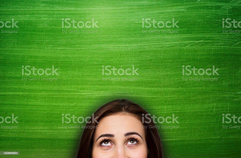 Woman in front of empty blackboard stock photo