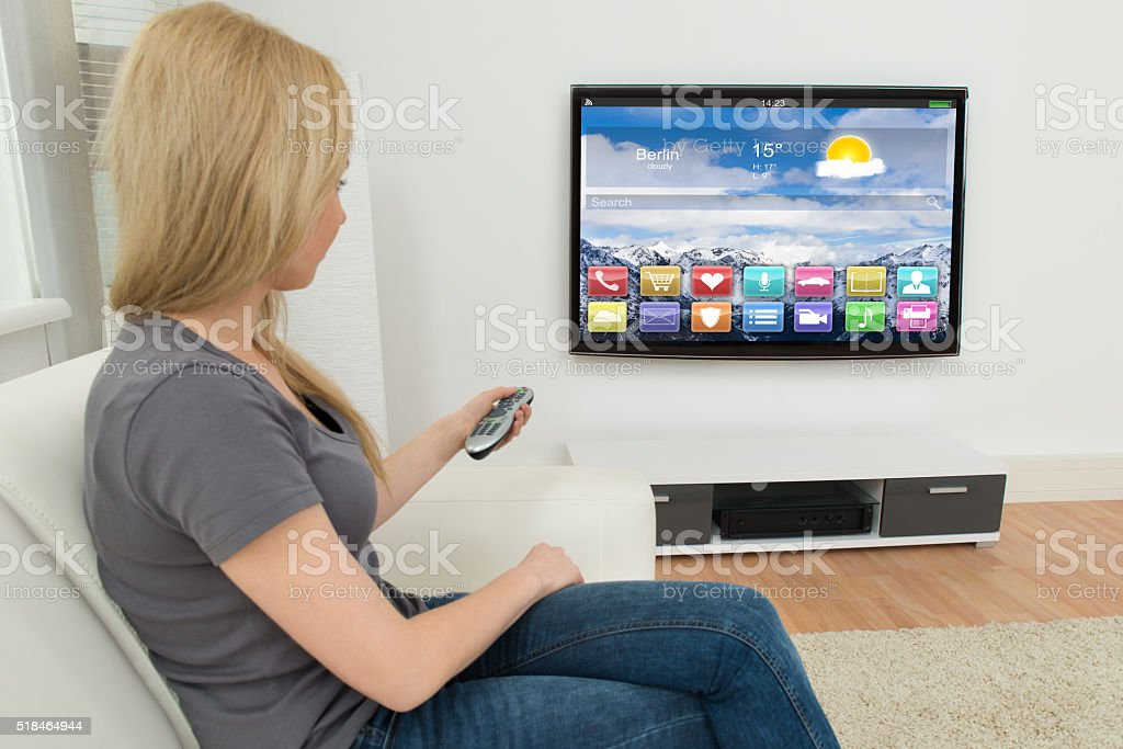 Woman In Front Of Television With Apps stock photo
