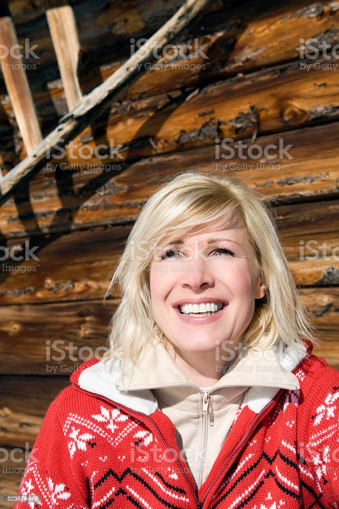 Woman in front of wooden wall, smiling, portrait, close-up stock photo