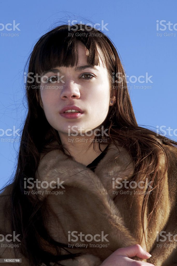Woman in fur coat looking foward stock photo