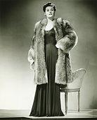 Woman in fur coat posing in studio, (B&W), portrait