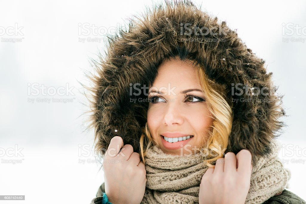 Woman in fur hood and scarf, snowy winter nature stock photo