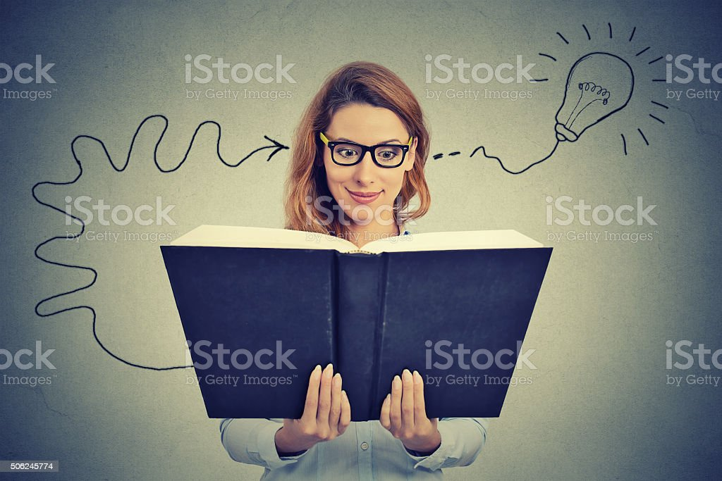 Woman in glasses reading book comes up with idea stock photo