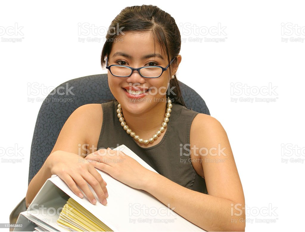 Woman in glasses sitting in an office chair holding folders stock photo