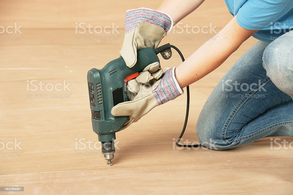 Woman in Gloves Drilling Plywood Floor royalty-free stock photo