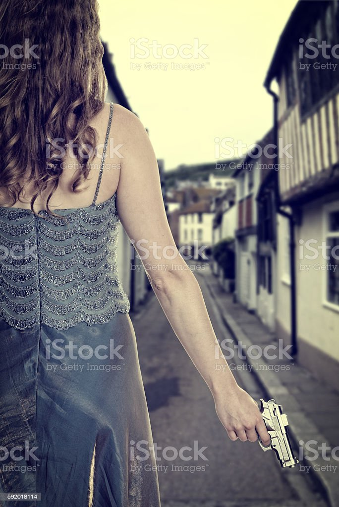 woman in gown with handgun on street stock photo