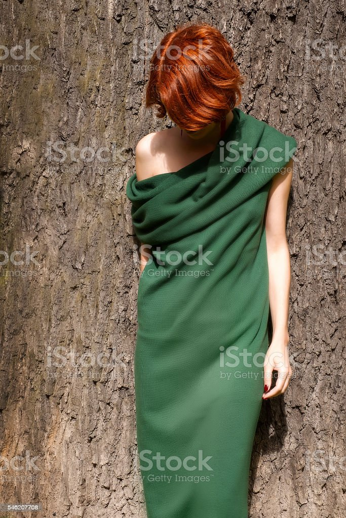 Woman in green dress against giant oak tree stock photo