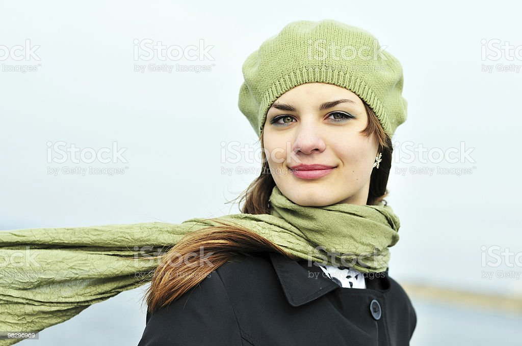 Woman in green hat and green scarf on a windy day royalty-free stock photo