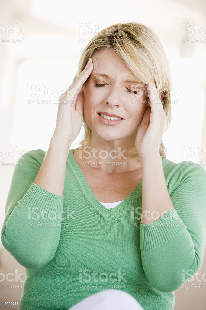 Woman in green shirt has a headache royalty-free stock photo