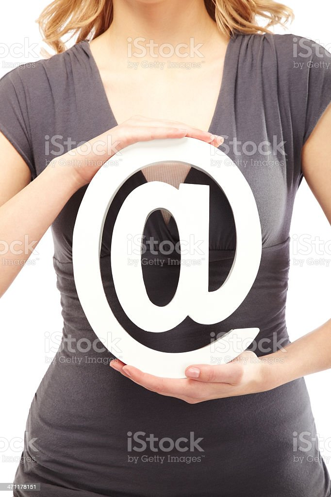 Woman in grey holding 'at' symbol royalty-free stock photo