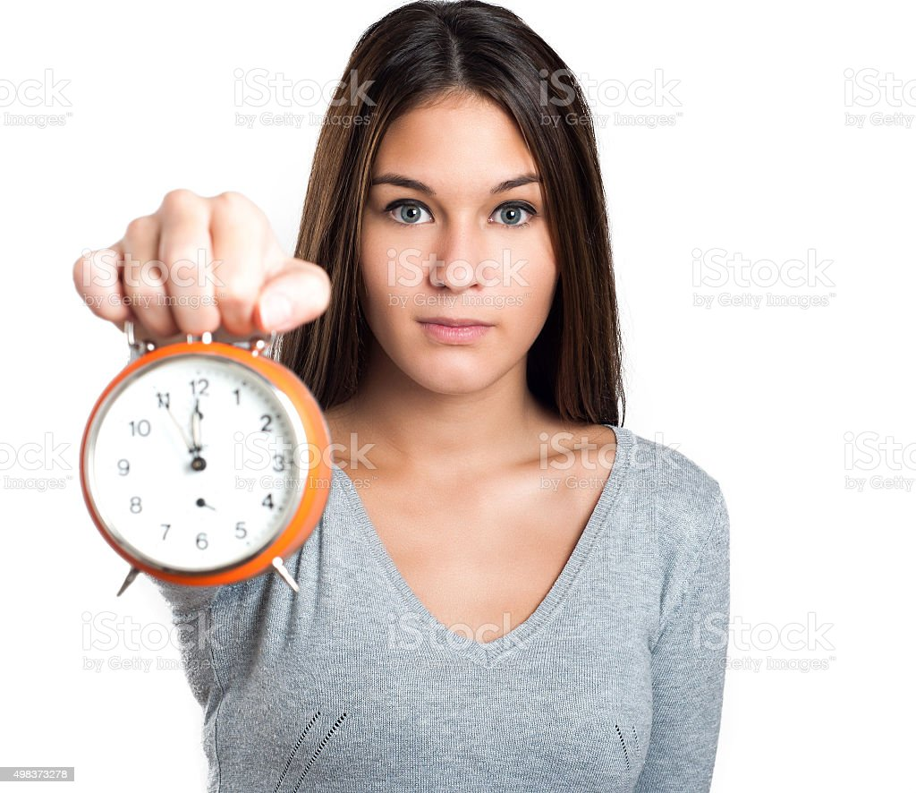 Woman in grey pullover showing the alarm clock stock photo