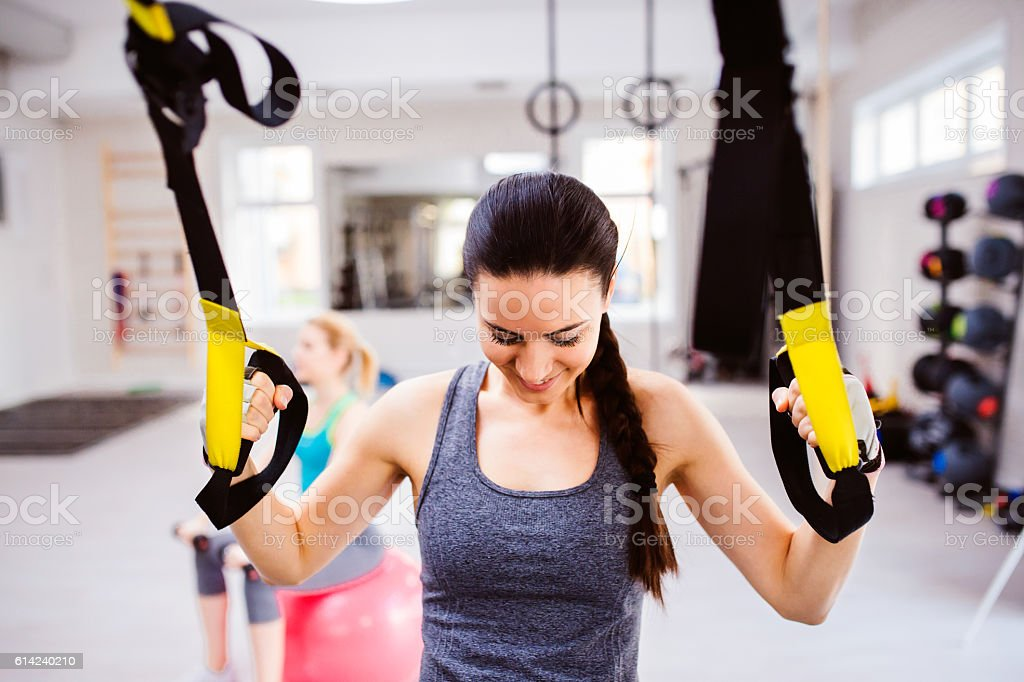 Woman in gym training arms with trx fitness strips stock photo