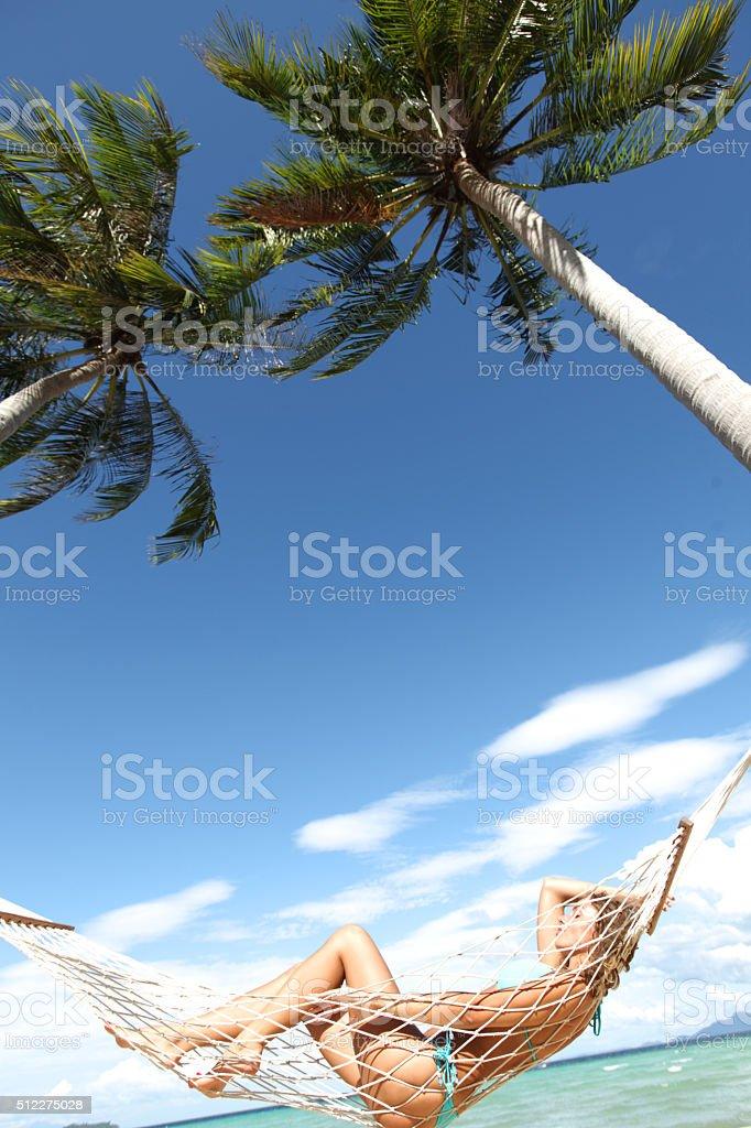 Woman in hammock on beach stock photo