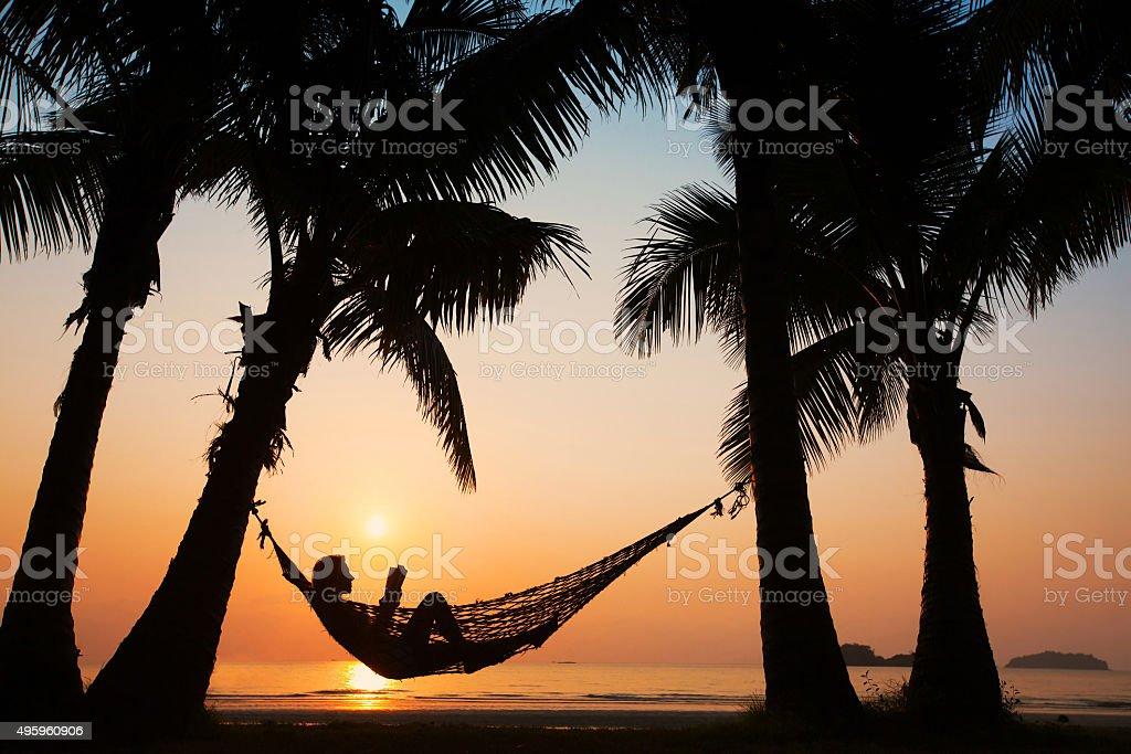woman in hammock on the beach stock photo