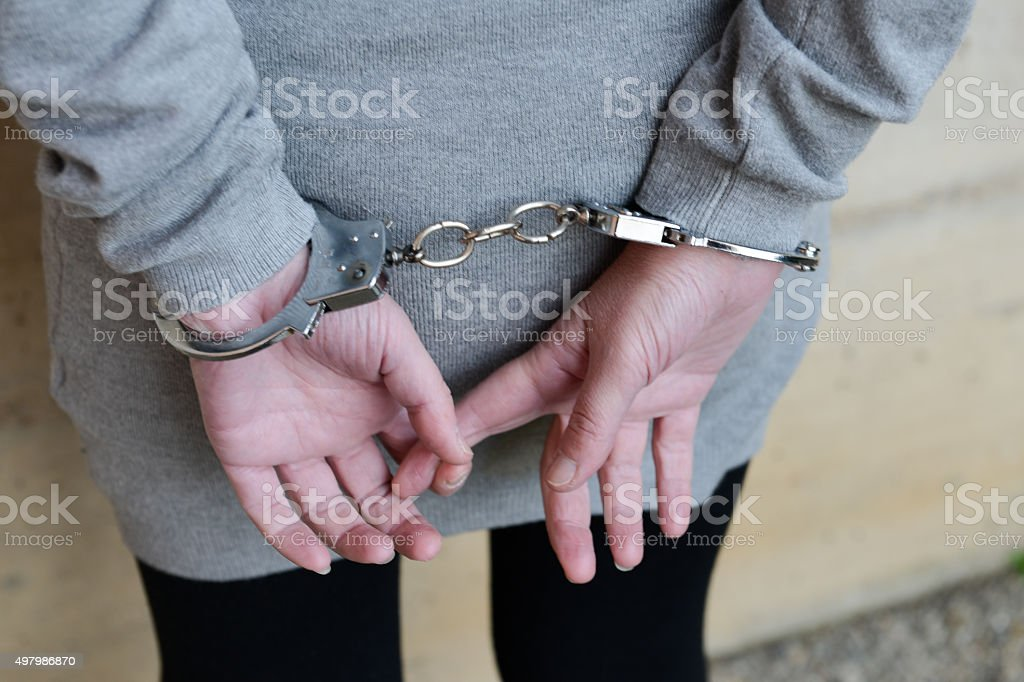 Woman in handcuffs behind her back stock photo