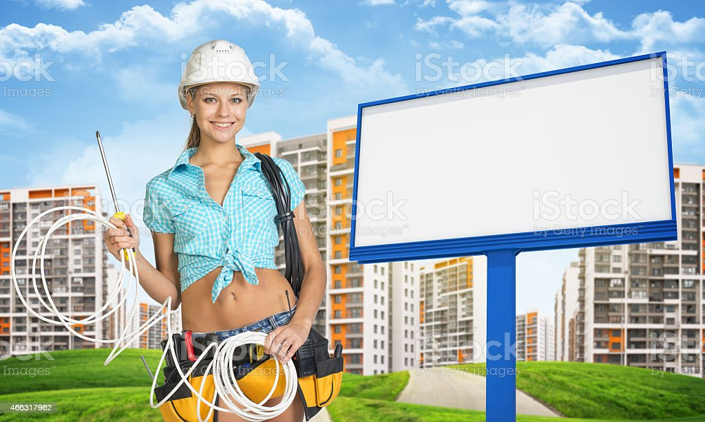 Woman in hard hat and tool belt holding coil of stock photo