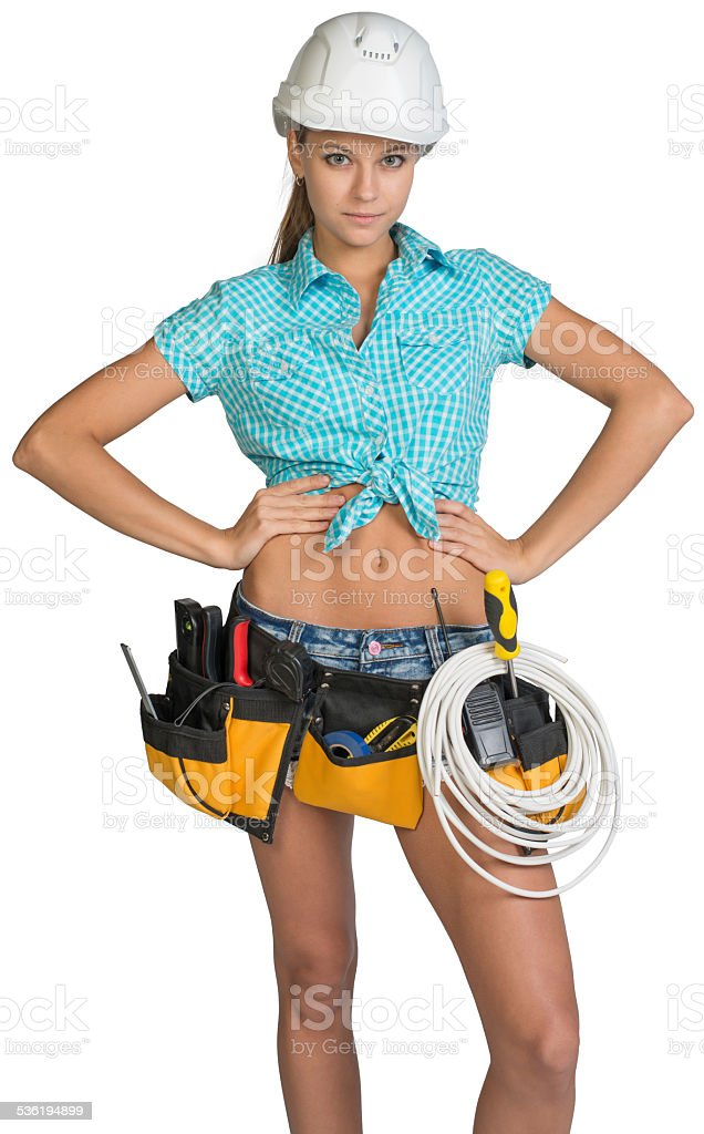 Woman in hard hat and tool belt posing stock photo